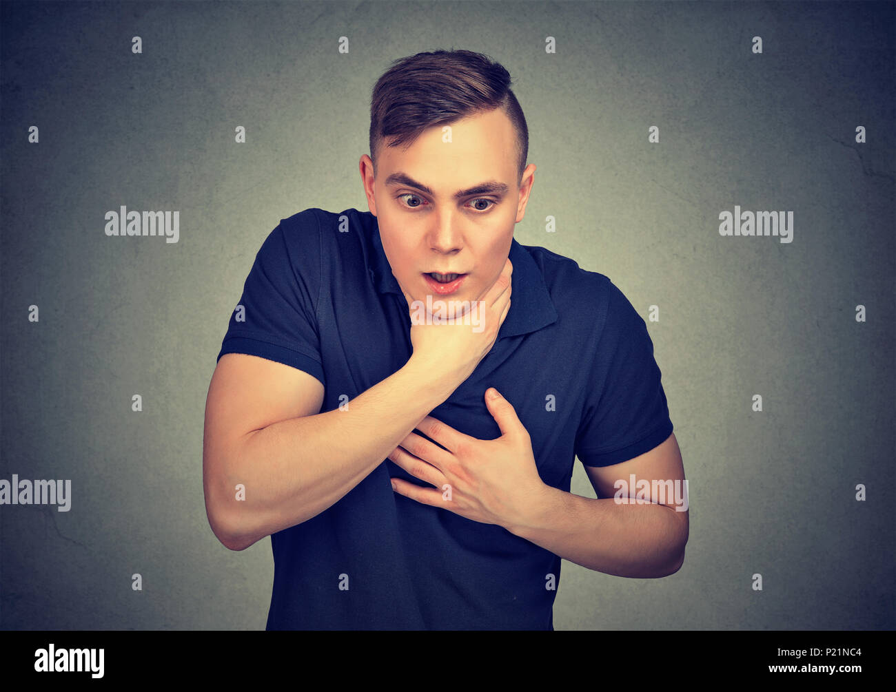 Young man having asthma attack or choking suffering from respiration problems isolated on gray background Stock Photo