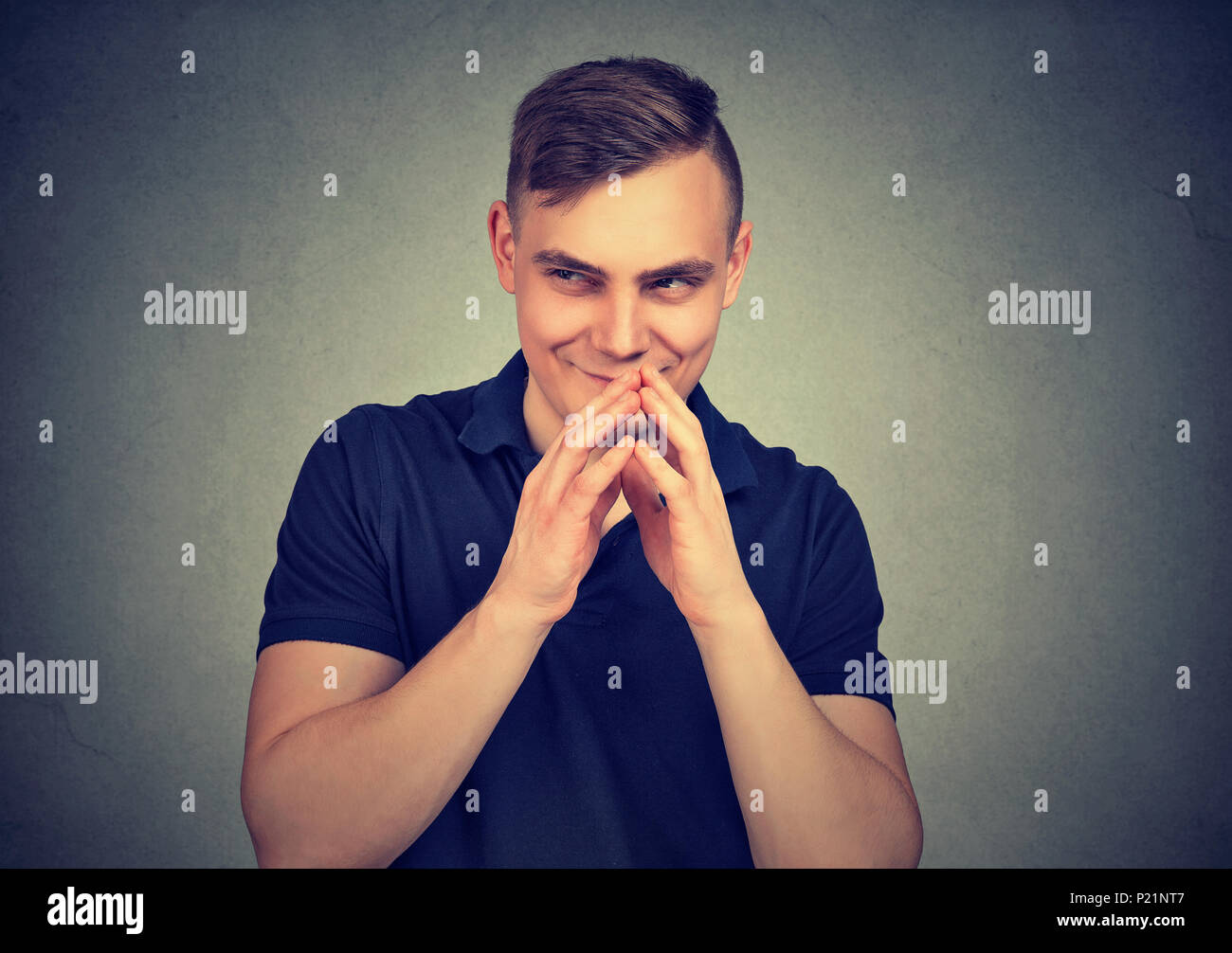 Sneaky man plotting something isolated on gray wall background. Negative human emotion facial expression feeling attitude - Stock Image