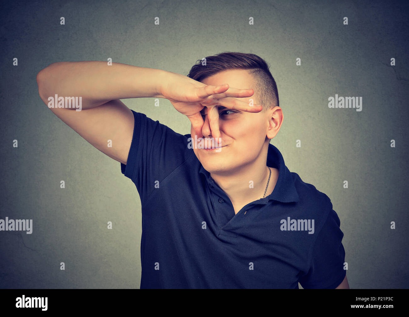 man pinches nose with fingers looks with disgust something stinks isolated on gray background. - Stock Image