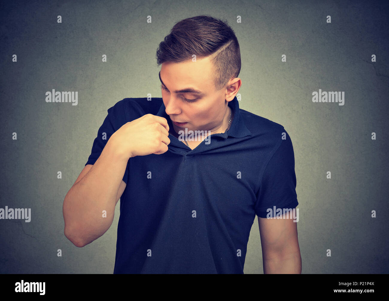 Man in awkward situation opening shirt to vent isolated on gray background. Human emotions facial expression, feelings - Stock Image