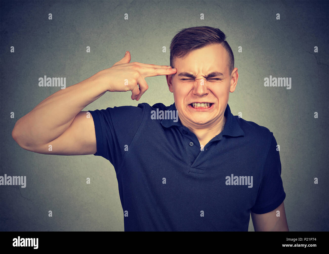 Portrait stressed man with finger gun gesture isolated on gray wall background. Negative human emotion - Stock Image