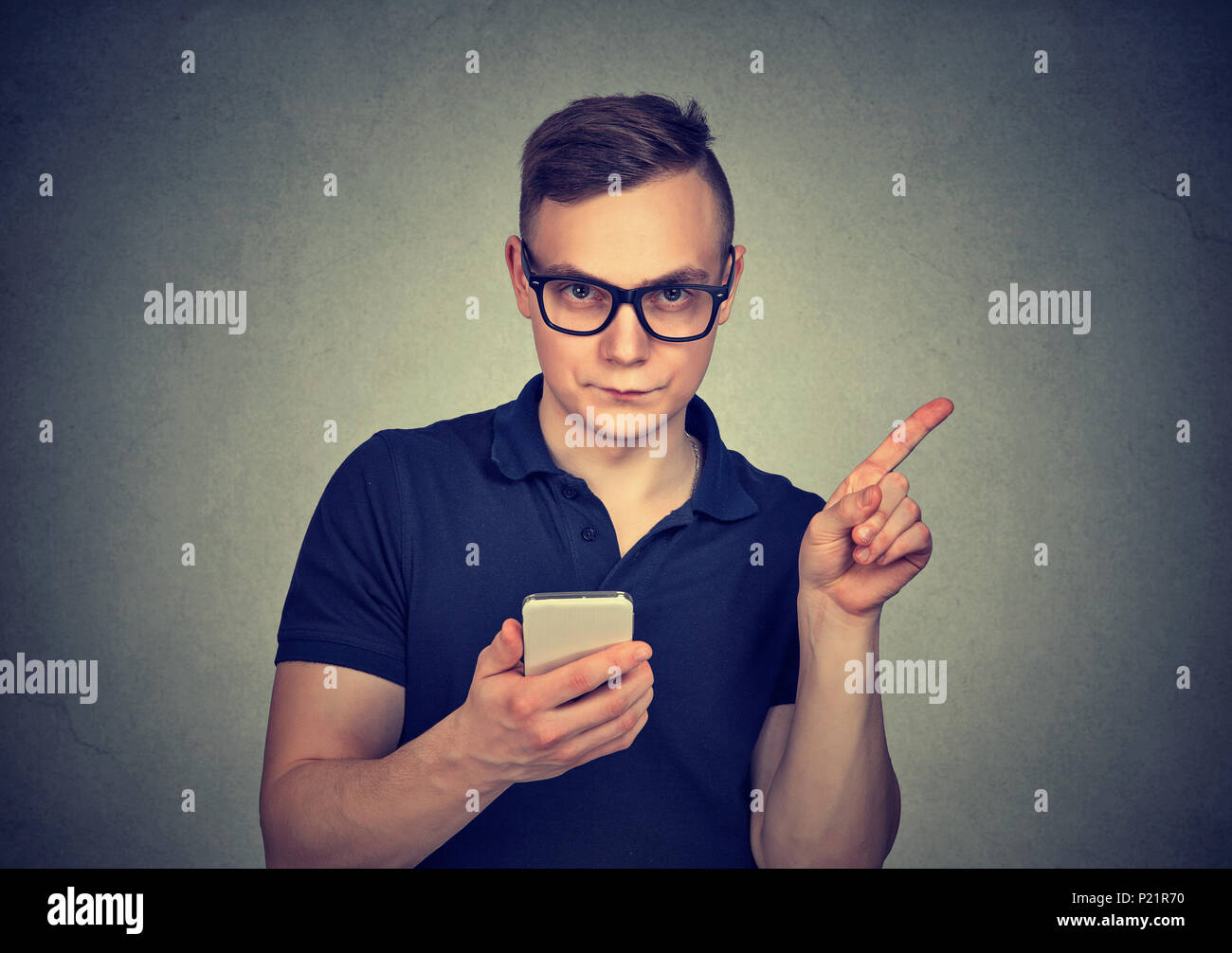 Man with smartphone showing no, attention with finger hand gesture. Blocking dangerous adult contents. Parental control concept - Stock Image