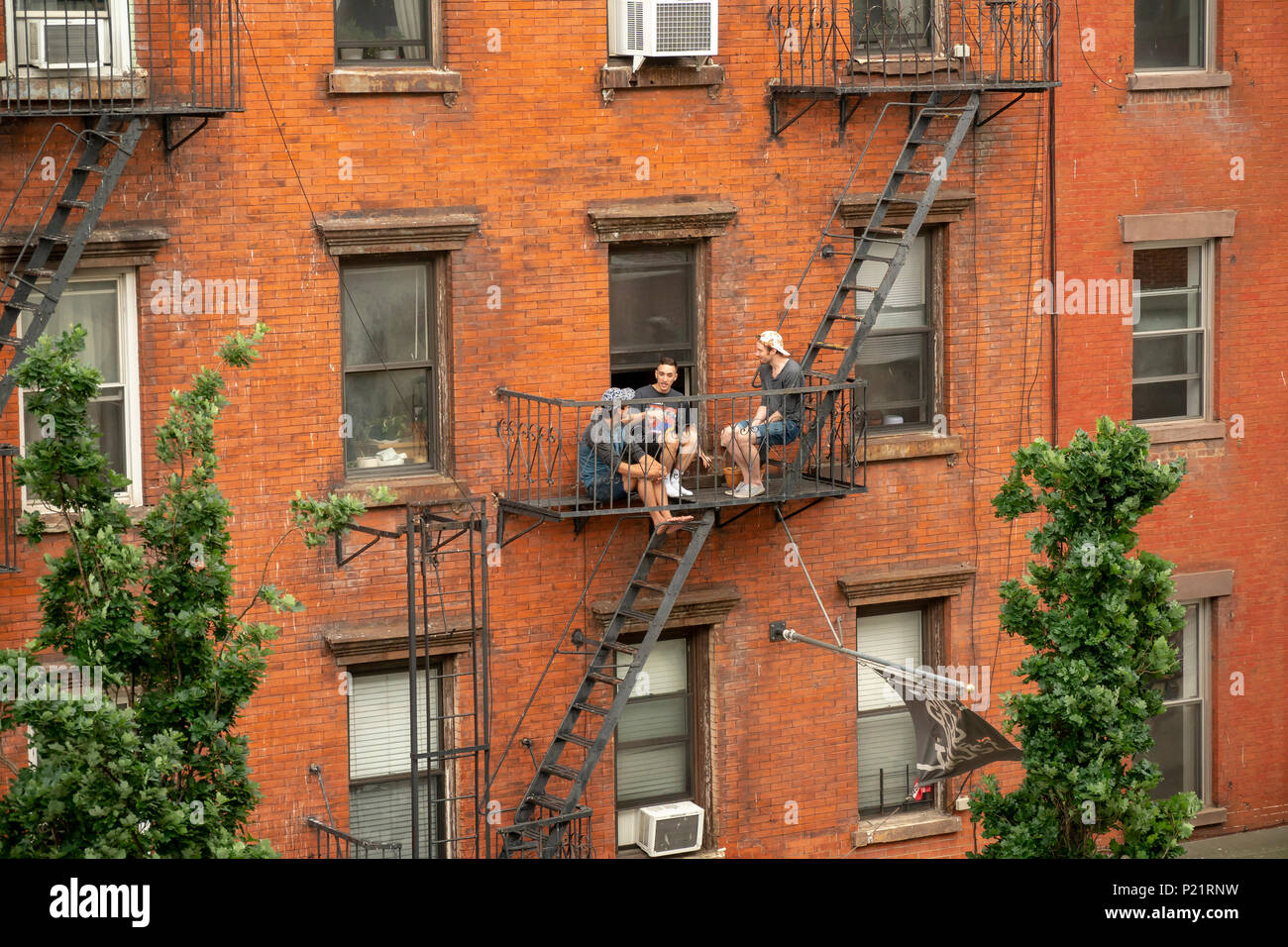 Residents hang out on a fire escape of their tenement in the Greenpoint neighborhood of Brooklyn on Sunday, June 3, 2018.   Zoning changes in 2005 promoted residential development in areas previously designated industrial.(© Richard B. Levine) - Stock Image