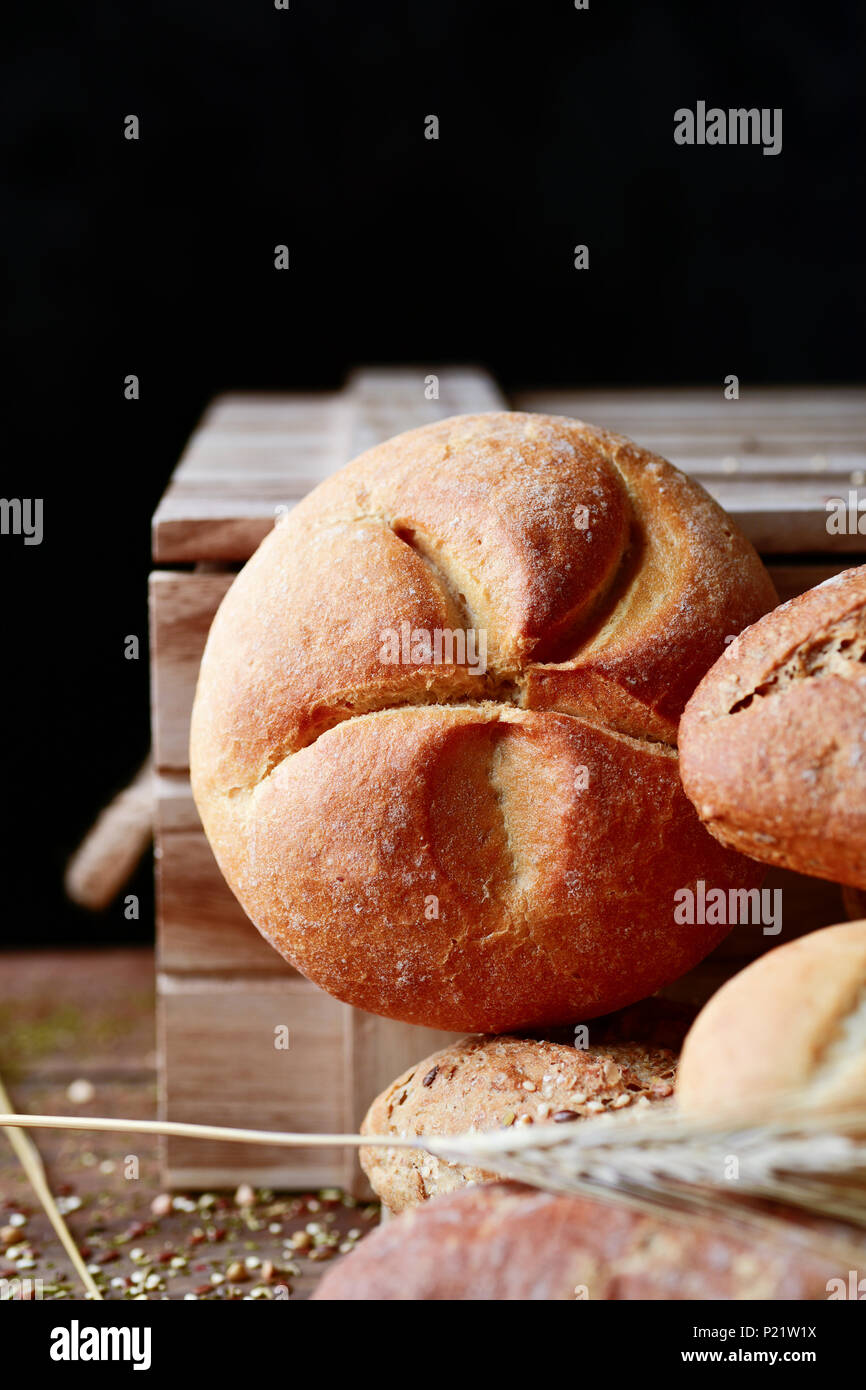 closeup of an assortment of different bread rolls and some wheat ears on a rustic wooden table, against a black background with some blank space on to - Stock Image
