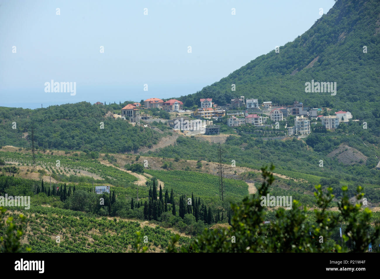 View of a small resort town Krasnokamenka and a lake situated at a foothill of a mountain, sea in the background. June 11, 2017. Crimea - Stock Image