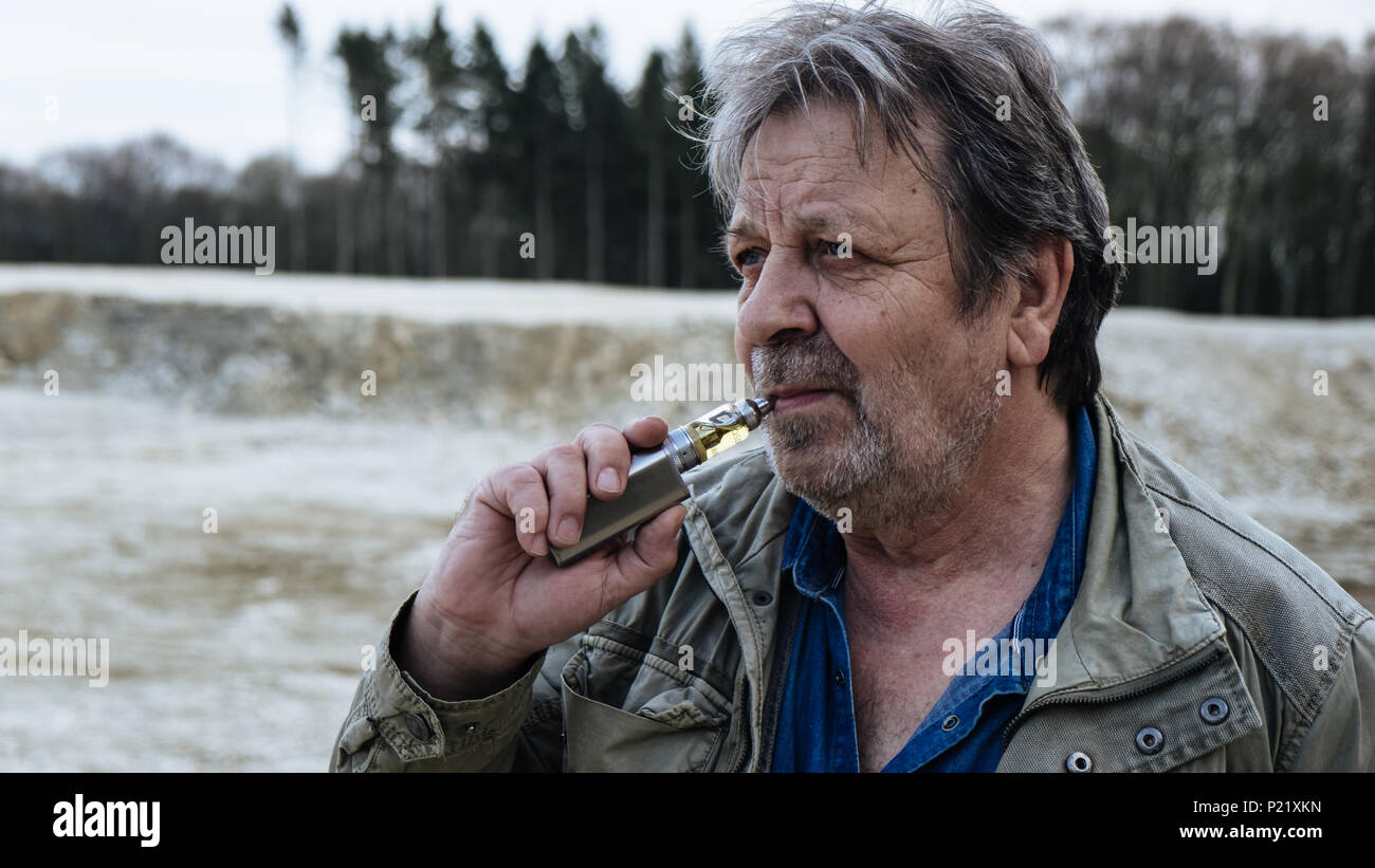 Old man with casual outfit is smoking e-cigarette in forest area - Stock Image