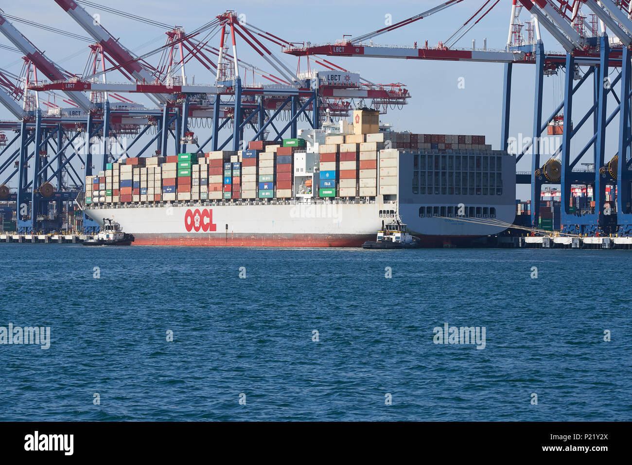 Container Ship, OOCL LONDON, About To Depart The Long Beach Container Terminal. Tugs Waiting Fore And Aft. Port Of Long Beach, California, USA. - Stock Image
