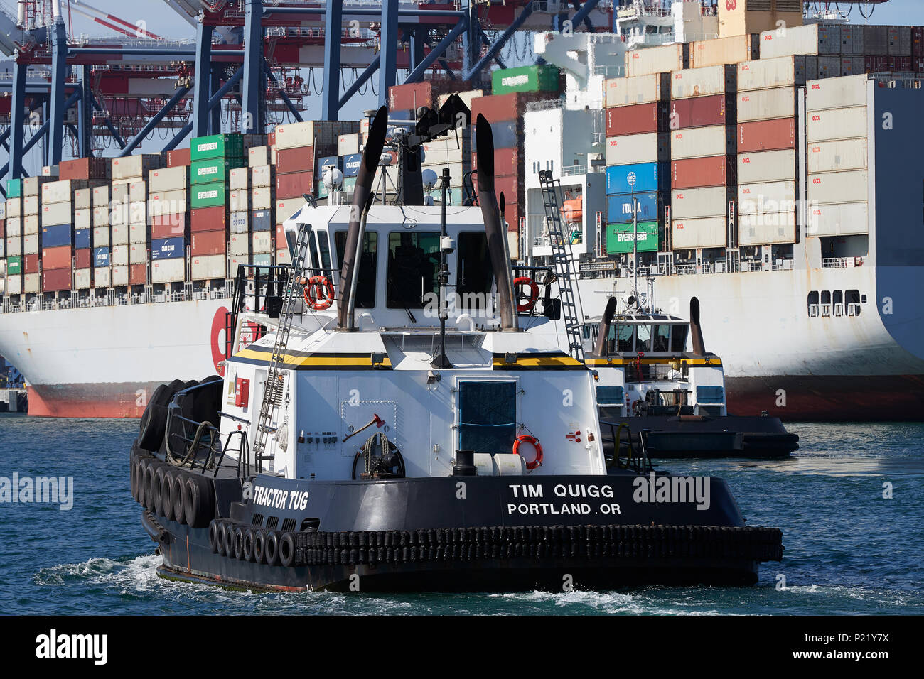 MILLENNIUM MARITIME, Tractor Tug, TIM QUIGG, Approached The OOCL Container Ship OOCL LONDON In The Port Of Long Beach, California, USA. - Stock Image