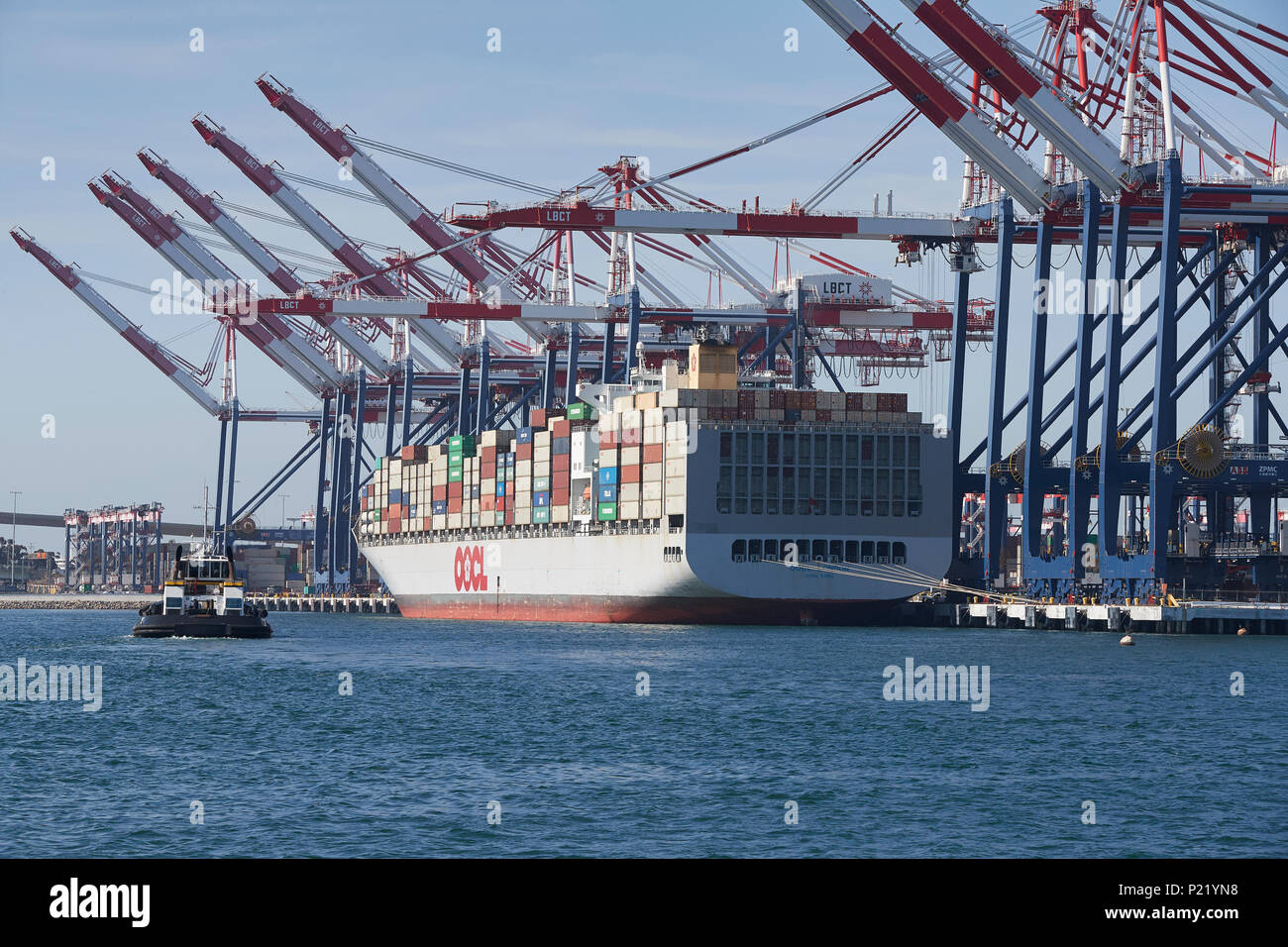 Container Ship, OOCL LONDON, About To Depart The Long Beach Container Terminal, A Tractor Tug Approaching The Ship. Port Of Long Beach, USA. - Stock Image