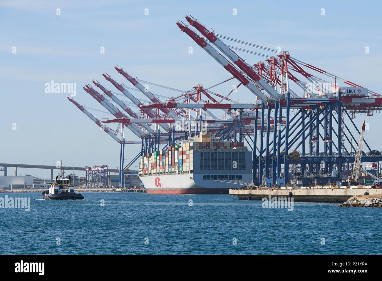 Giant Container Ship, OOCL LONDON, About To Depart The Long Beach Container Terminal, A Tractor Tug Approaching The Ship. - Stock Image