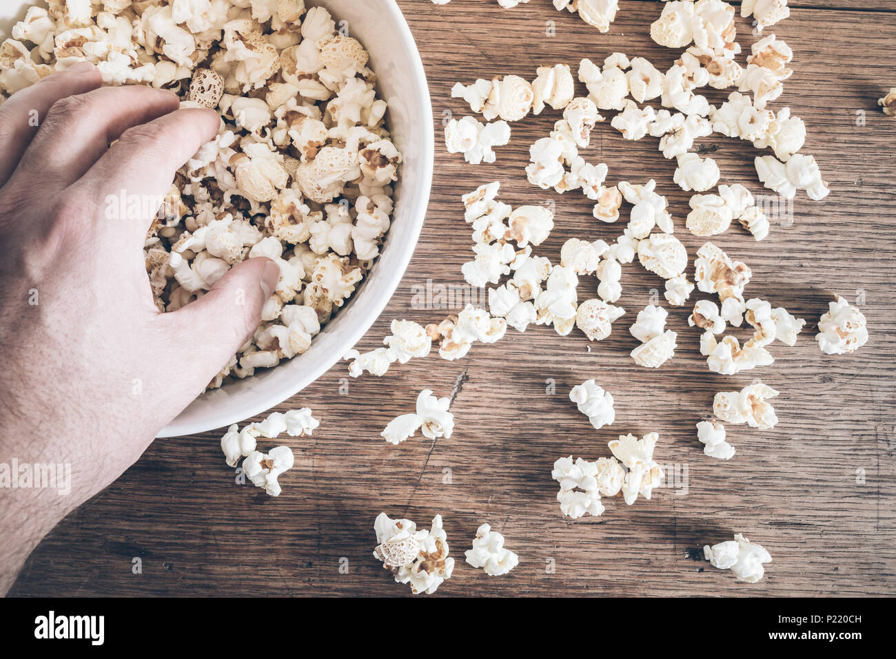 directly above shot of hand grabbing popcorn from bowl on rustic wooden table - Stock Image