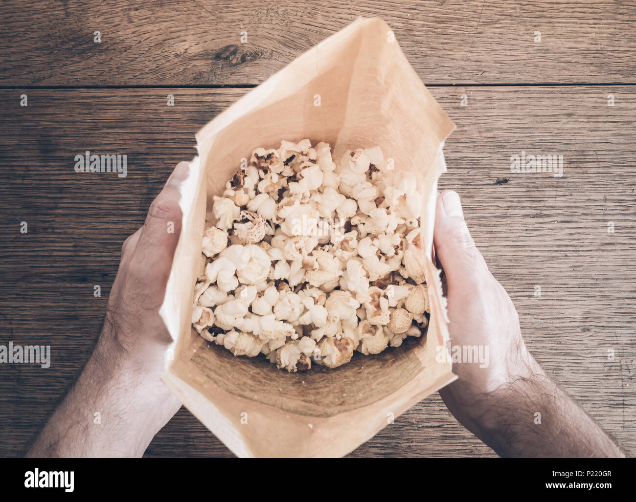 directly above shot of hands holding brown paper bag filled with popcorn - Stock Image