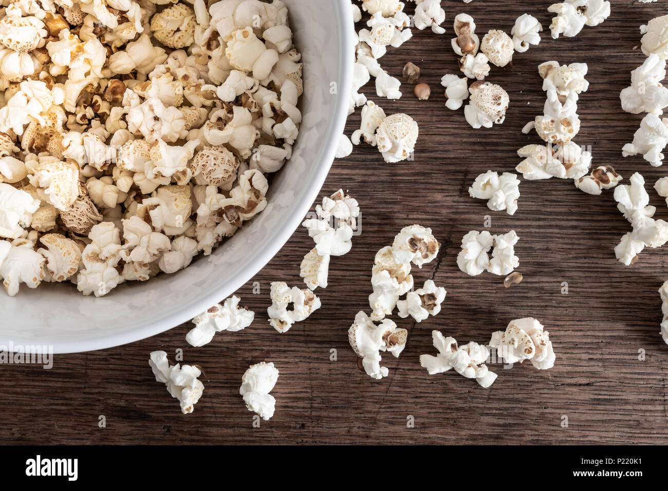 directly above close-up of bowl filled with popcorn on rustic wooden table - Stock Image