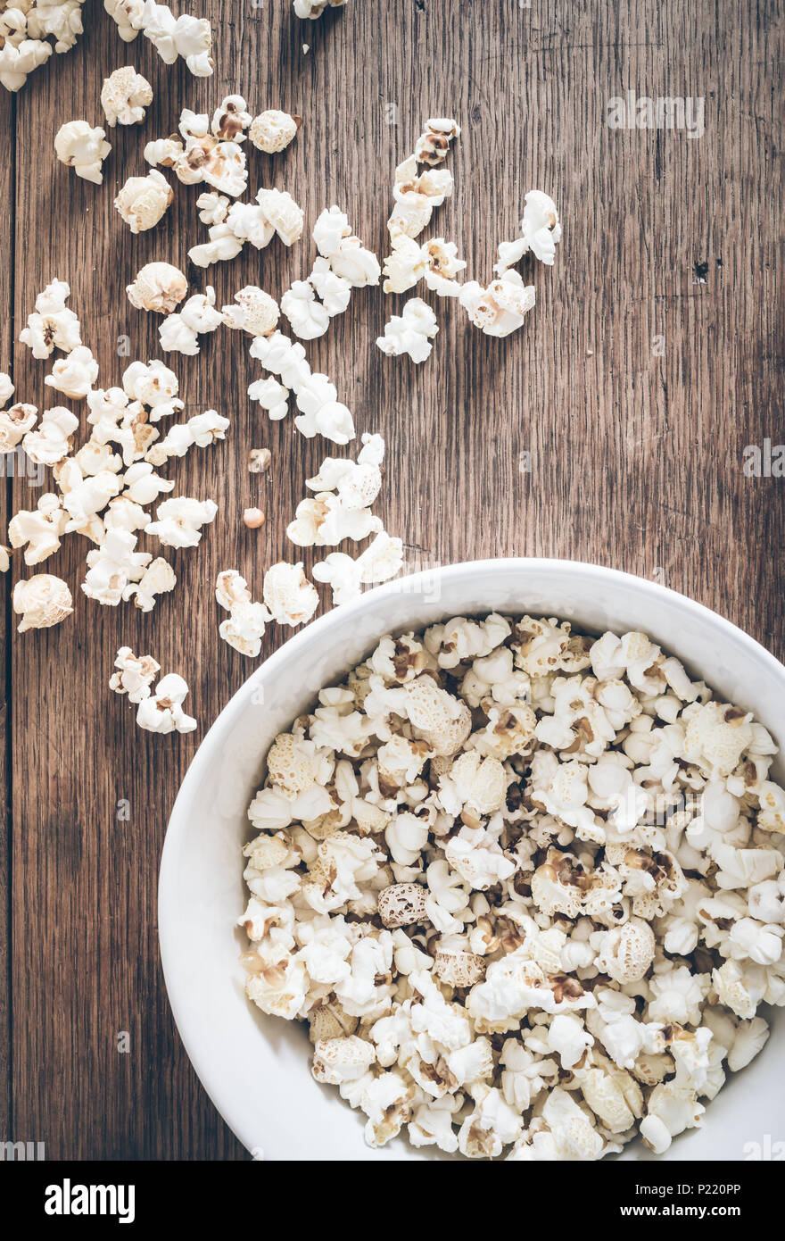 directly above shot of bowl filled with popcorn and spilled popcorn on rustic wooden table - Stock Image