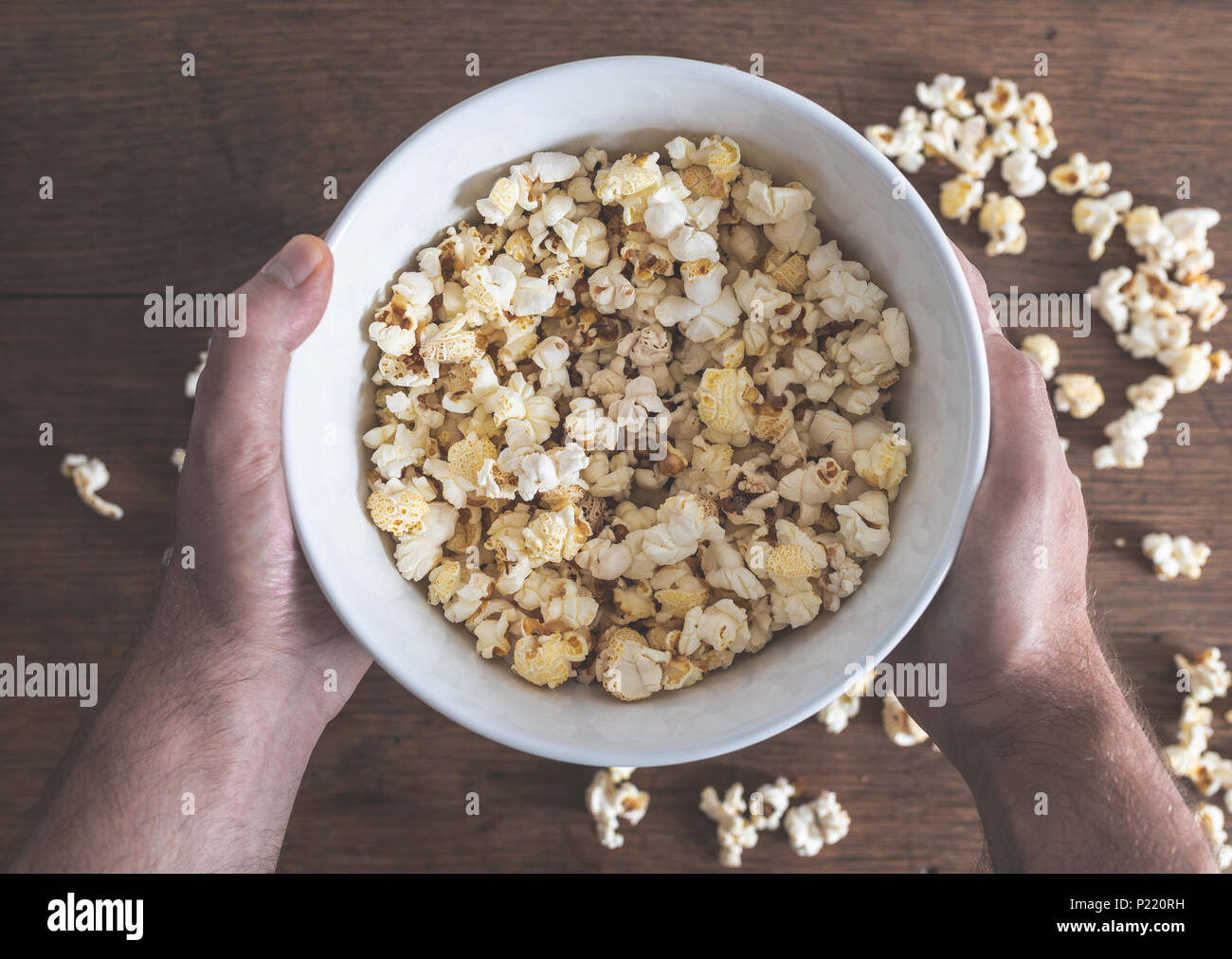 hands holding bowl filled with popcorn above wooden table - Stock Image