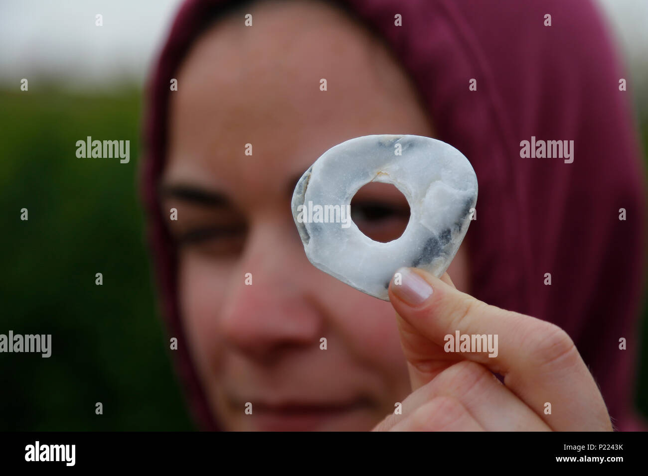 Girl in hooded top looking through hole in stone - Stock Image