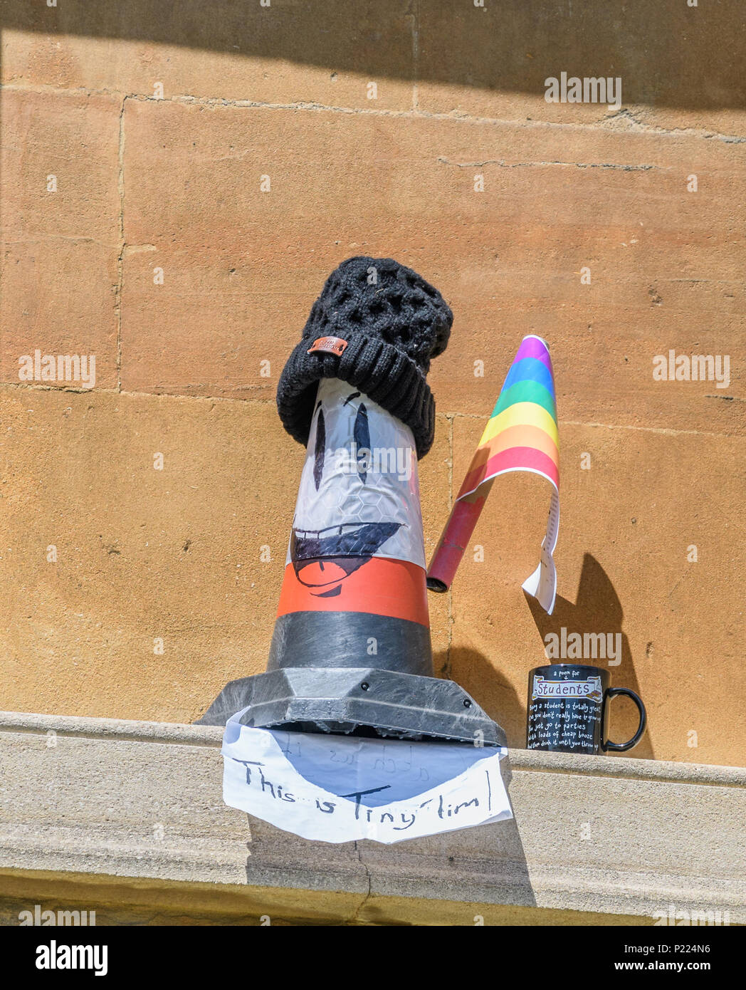 An image Tiny Tim, and a mug praising the indolence of student life, on a ledge of the Radcliffe Camera Bodleian library at the university of Oxford,  - Stock Image