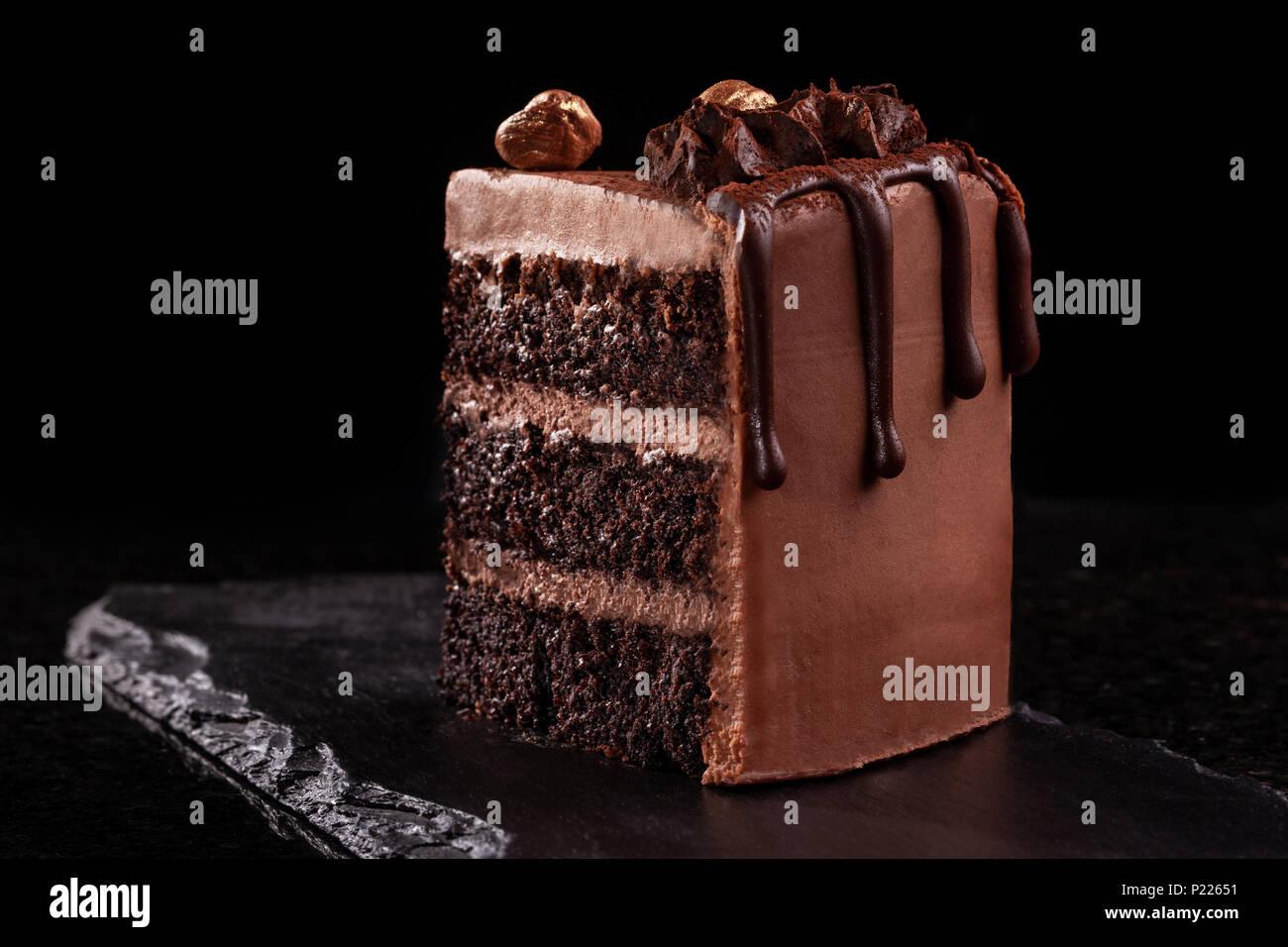 Piece of chocolate cake. Chocolate mousse cake slice on a black board, black background. - Stock Image