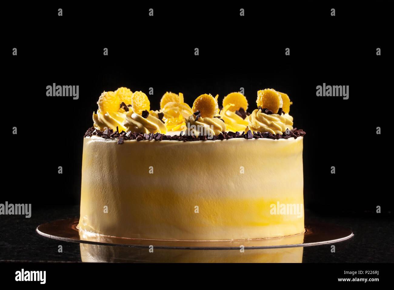 Round yellow birthday cake. Decorative cream decorations on the cake. Black background. - Stock Image