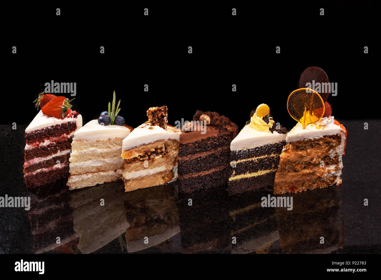Assorted large pieces of different cakes: chocolate, raspberries, strawberries, nuts, blueberries. Pieces of cakes on a black table. - Stock Image