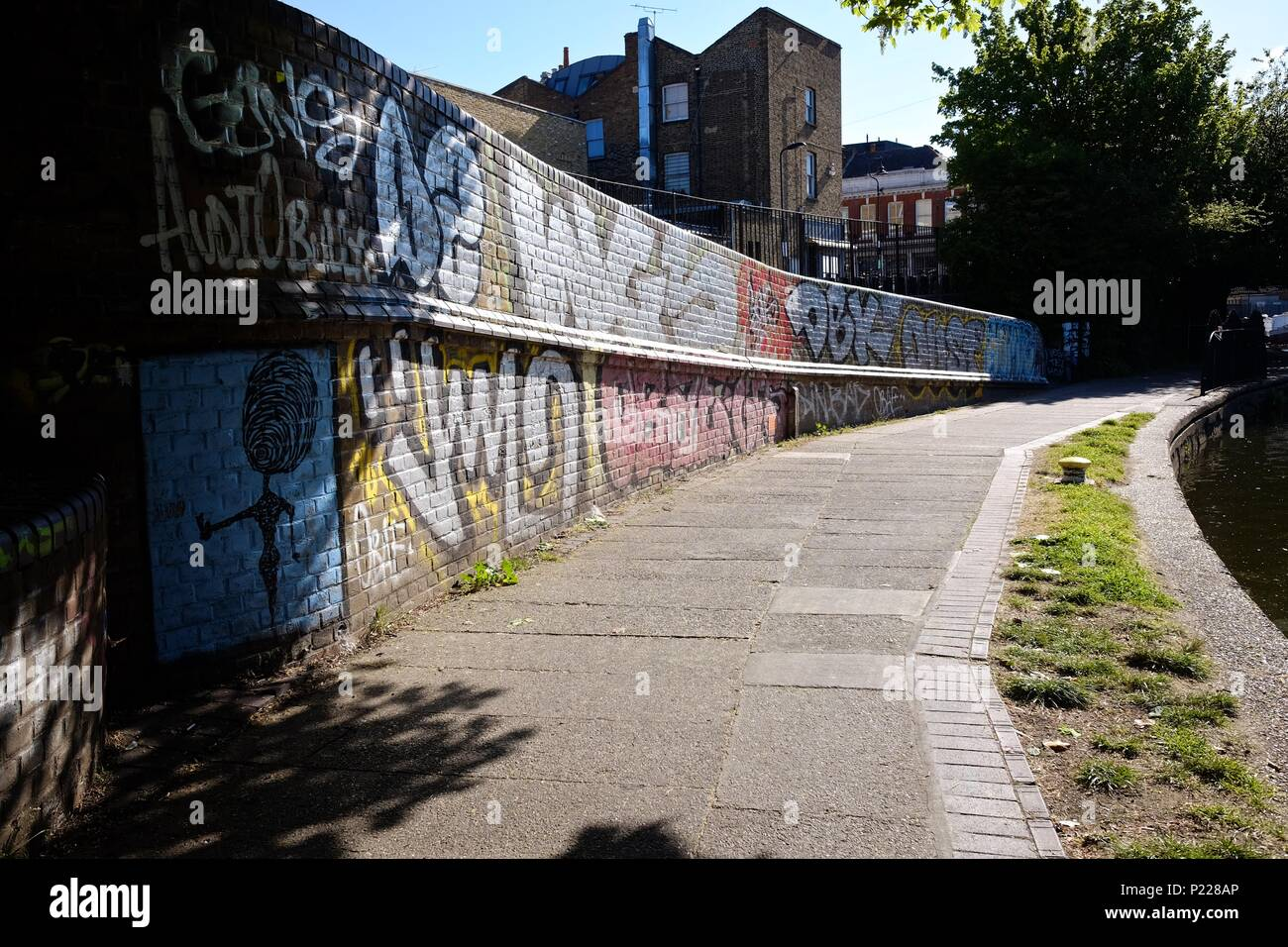 Graffiti alongside towpath to a canal in London - Stock Image