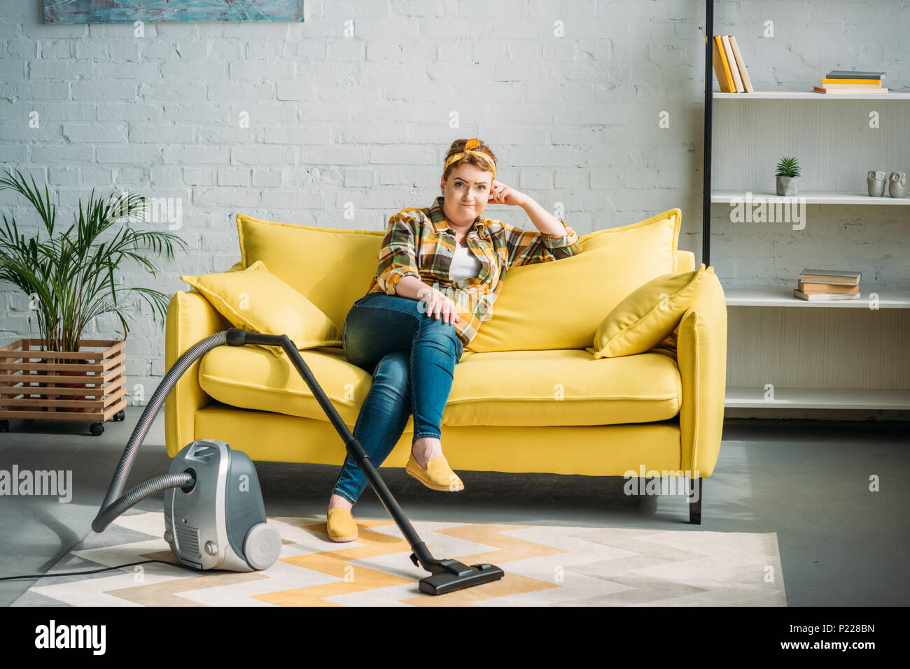 grimacing woman sitting on sofa and looking at camera, vacuum cleaner on floor at home - Stock Image