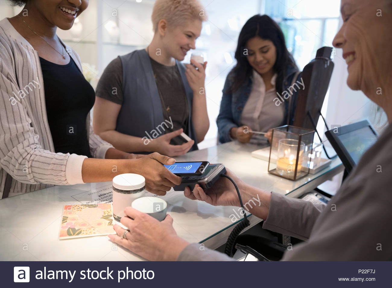 Young women with smart phone paying with contactless payment in boutique Stock Photo