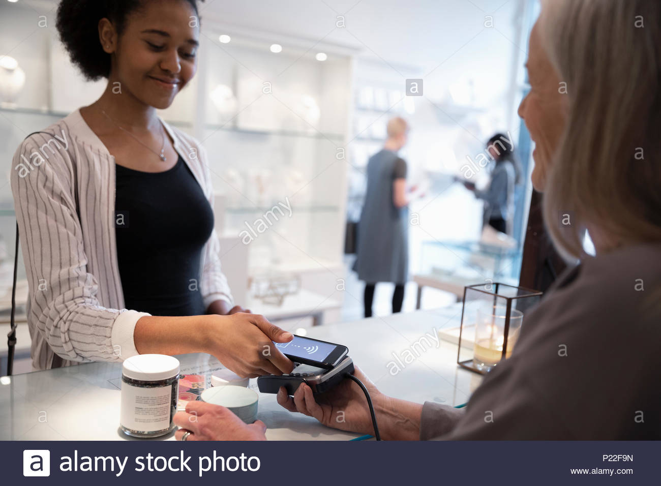 Young woman with smart phone paying with contactless payment in boutique - Stock Image