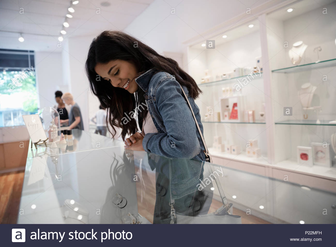 Young woman shopping for jewelry at display case in boutique - Stock Image