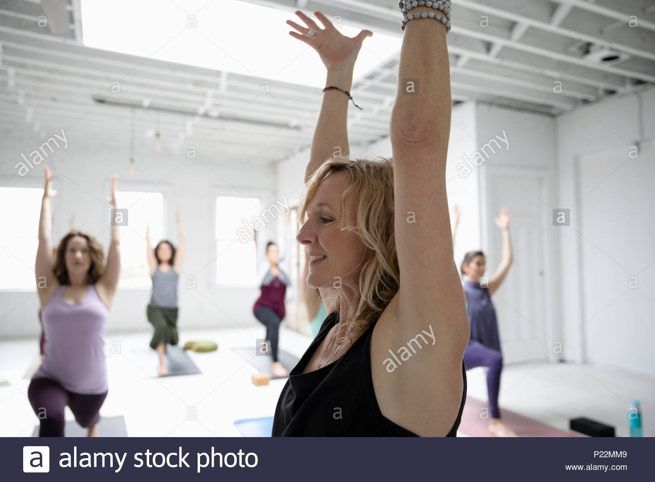 Smiling woman practicing yoga warrior one pose in yoga class - Stock Image
