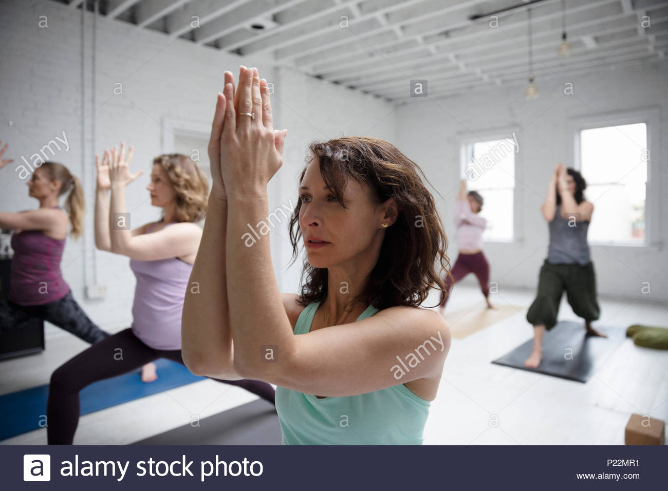 Focused woman practicing yoga warrior one pose in yoga class - Stock Image