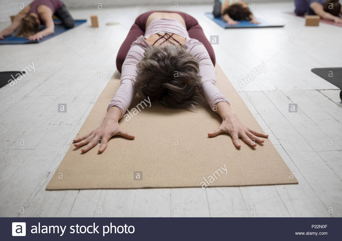 Woman practicing yoga child - Stock Image