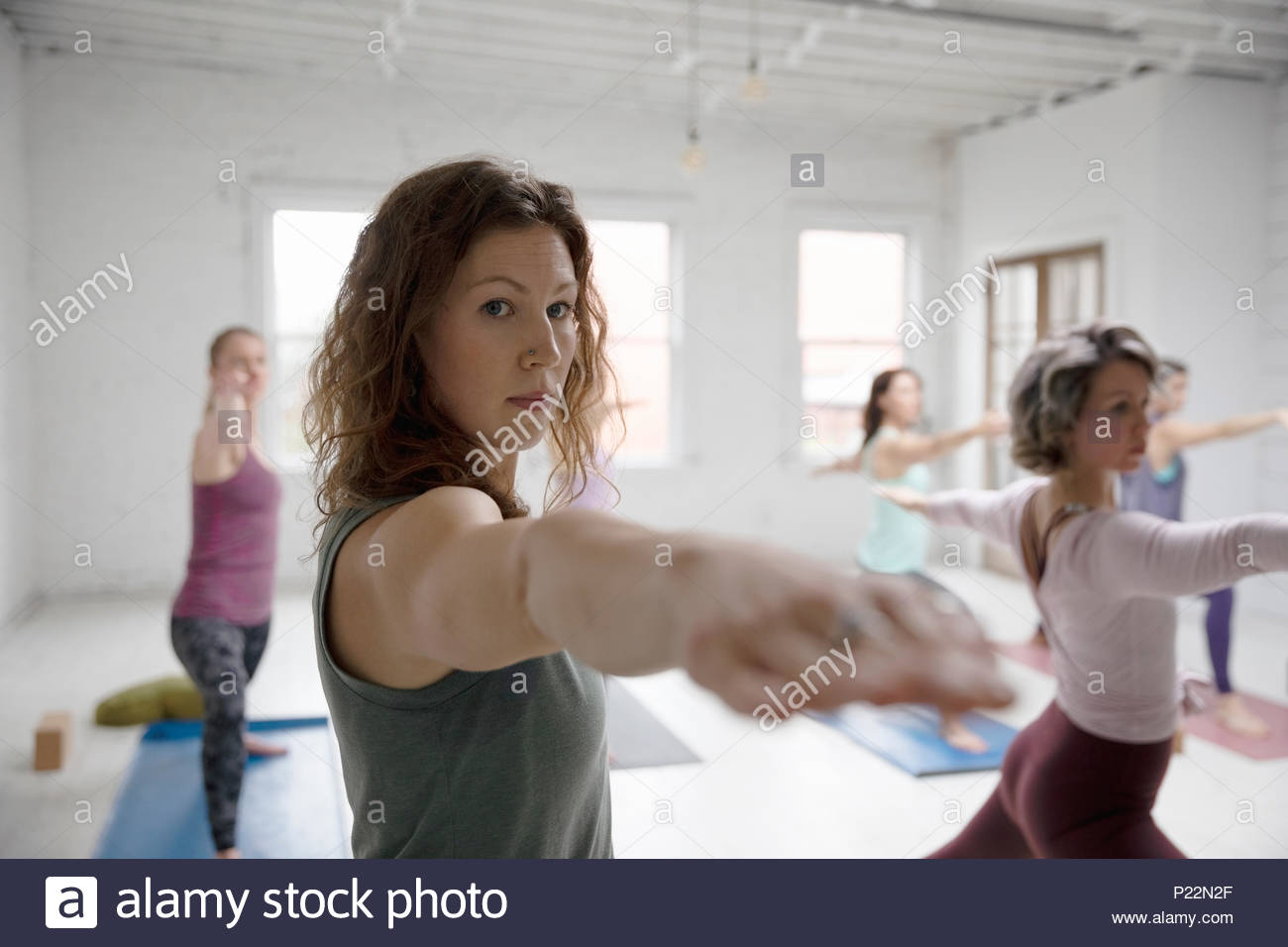 Focused woman practicing yoga warrior two pose in yoga class - Stock Image