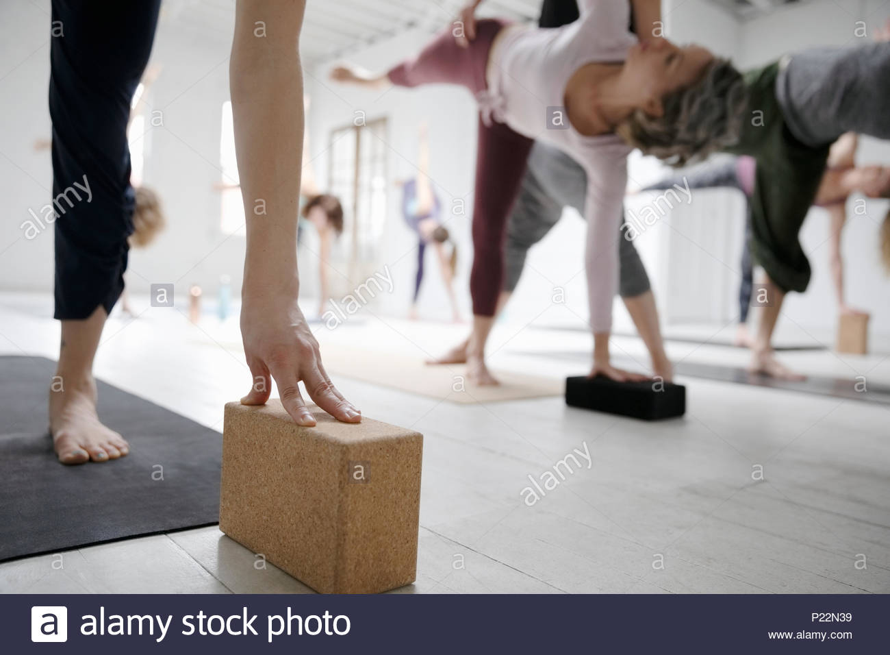 Women practicing half moon pose with blocks in yoga class - Stock Image