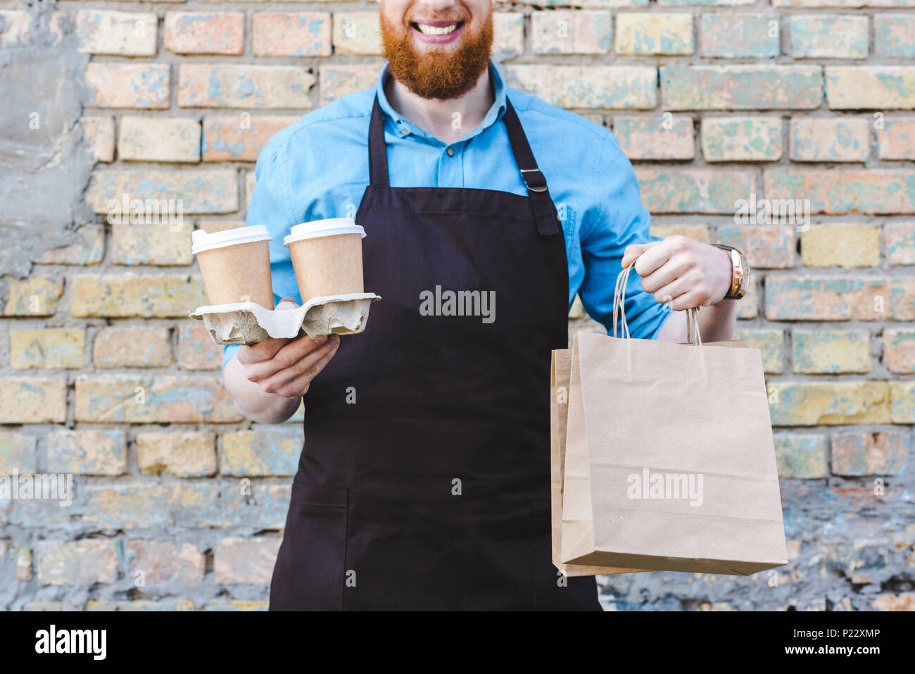 cropped shot of smiling male barista in apron holding paper bags and disposable cups with coffee - Stock Image
