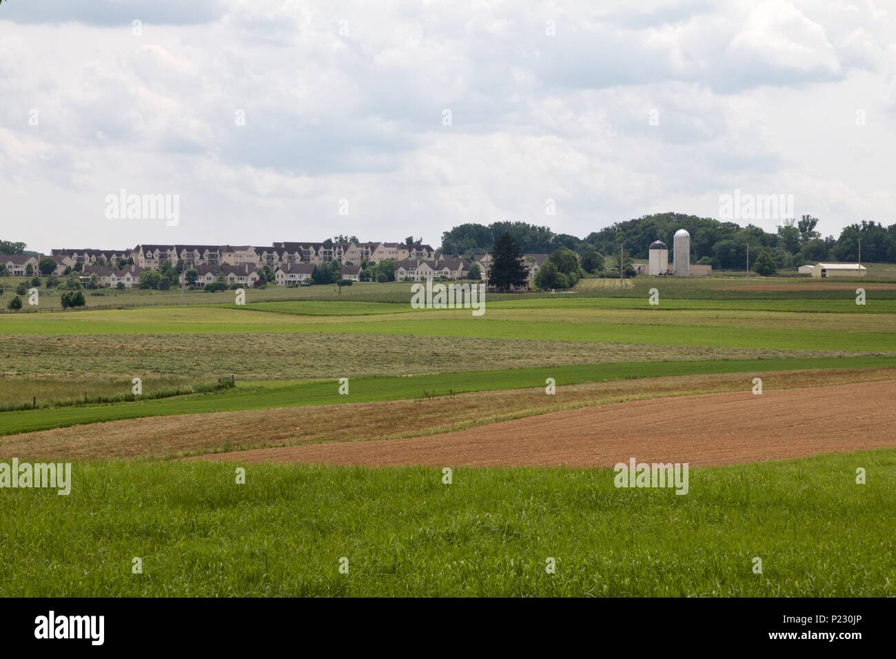 Urban sprawl marks the boundary of Natural Land Trust protected farmland in Montgomery County, Pennsylvania. - Stock Image