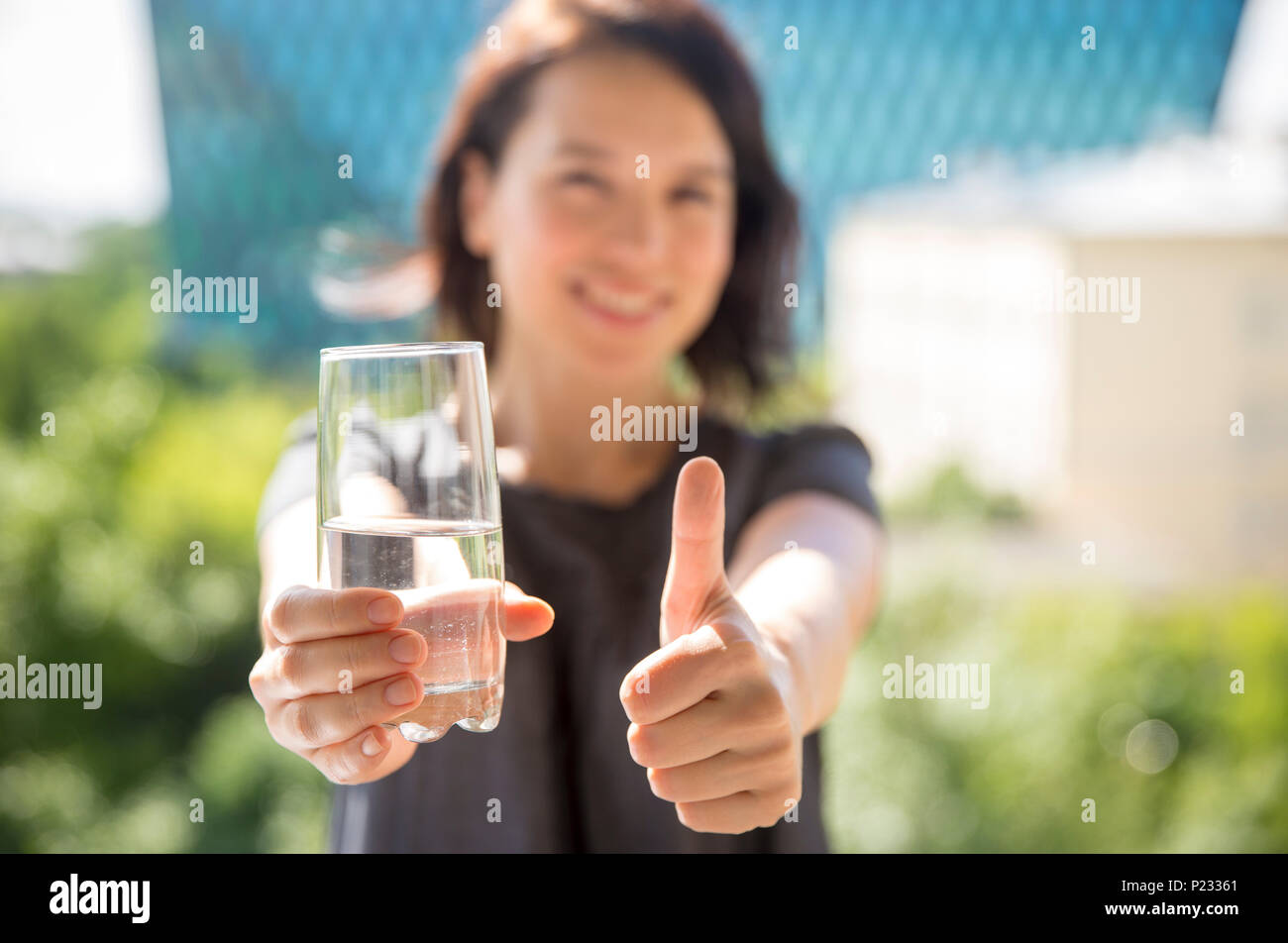 Young woman holding a glass of water recommend drinking water with thumb up - Stock Image