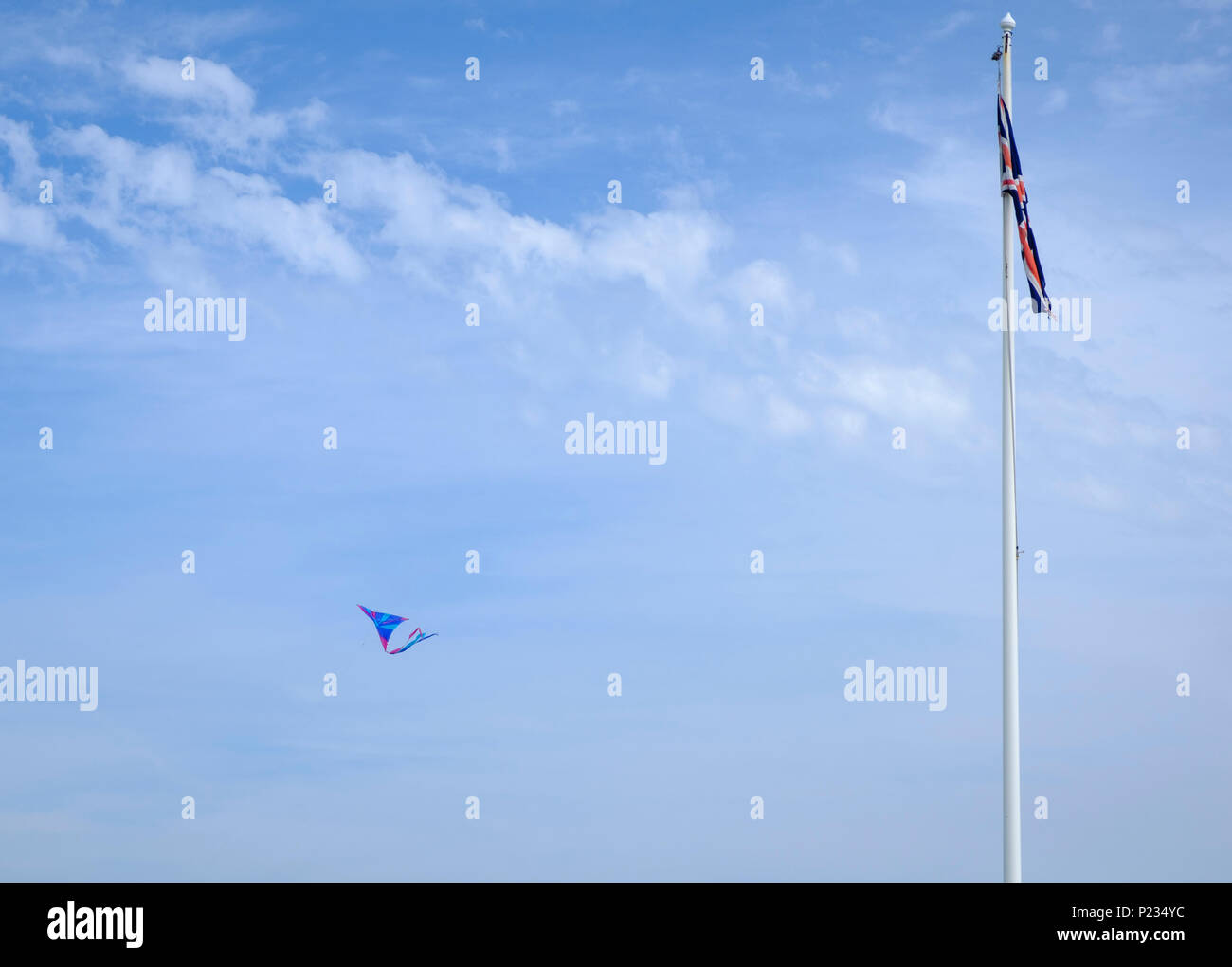 Union Jack Flag on flagpole against a blue sky with a kite being flown nearby - Stock Image
