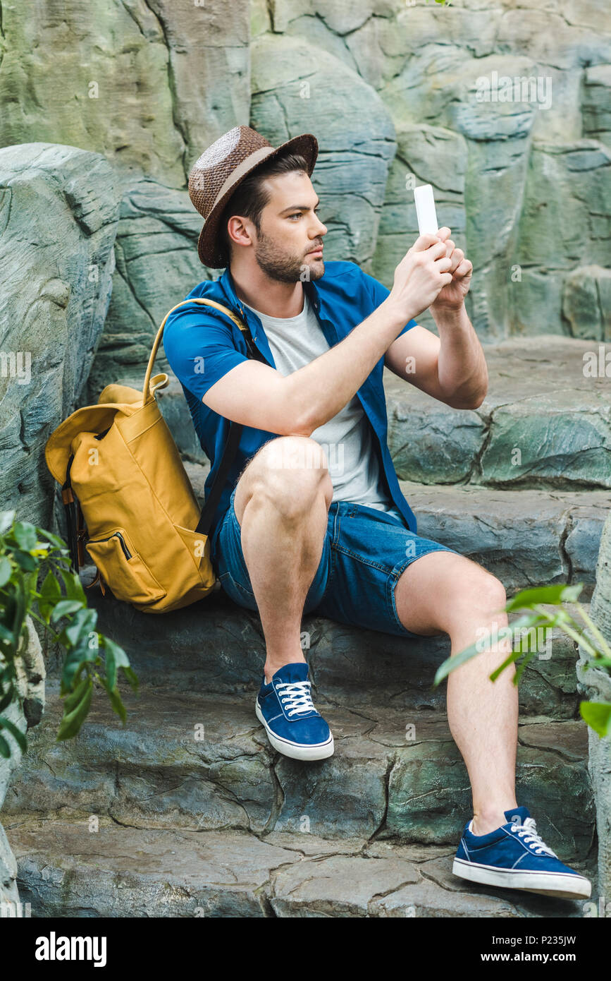 handsome young man taking photo with smartphone while sitting on stone staircase - Stock Image
