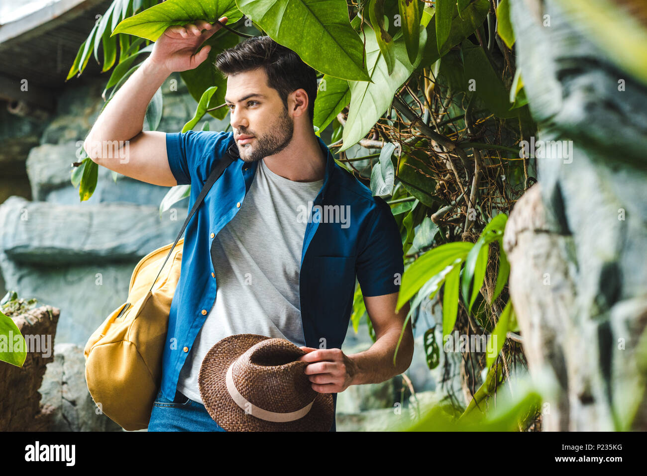 handsome young man in stylish clothes with straw hat in rainforest Stock Photo