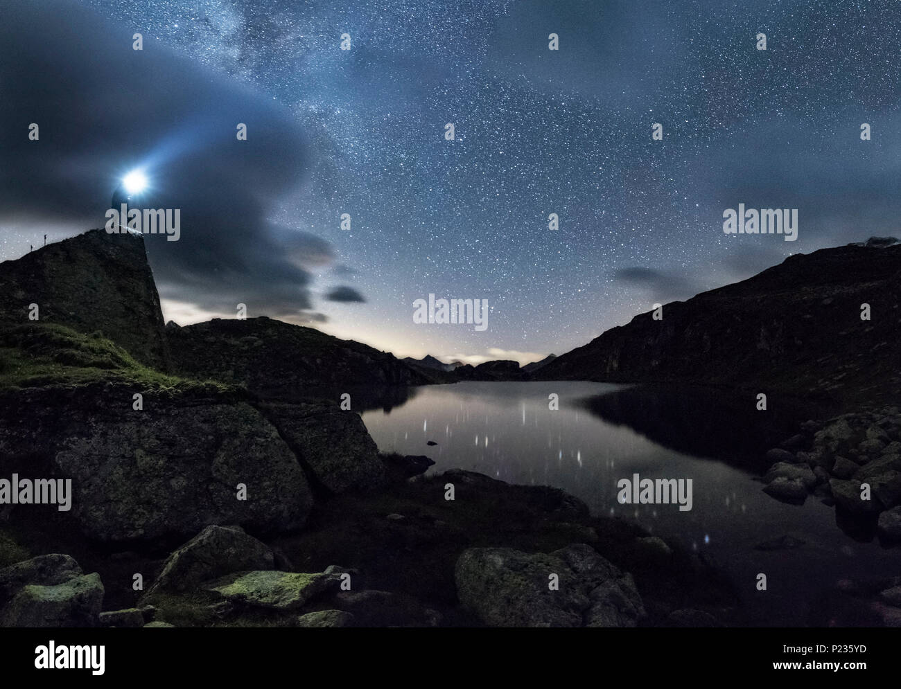 Selfportrait on a mountain lake at the Pfitscherjoch, parts of the Milky Way seen behind the clouds, reflexions of the stars in the water, thunderclouds. Hiker with headlamp - Stock Image