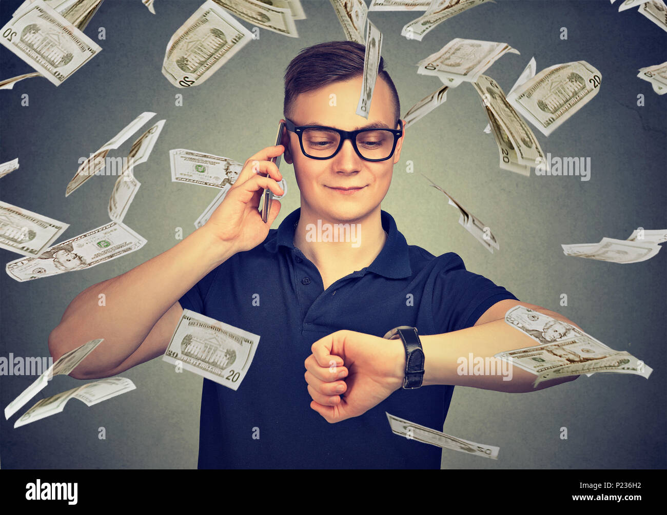 Busy businessman looking at wrist watch, talking on mobile phone under cash rain. Time is money concept - Stock Image