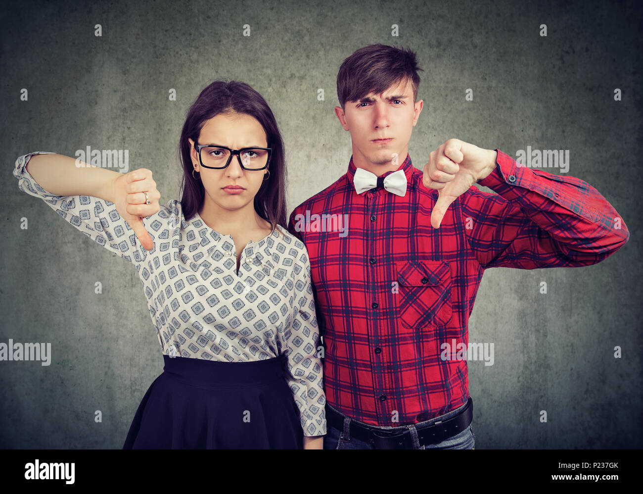 Unhappy grumpy couple giving thumbs down gesture, disagree with something. Displeased young man and woman express nbegative emotions and feelings - Stock Image