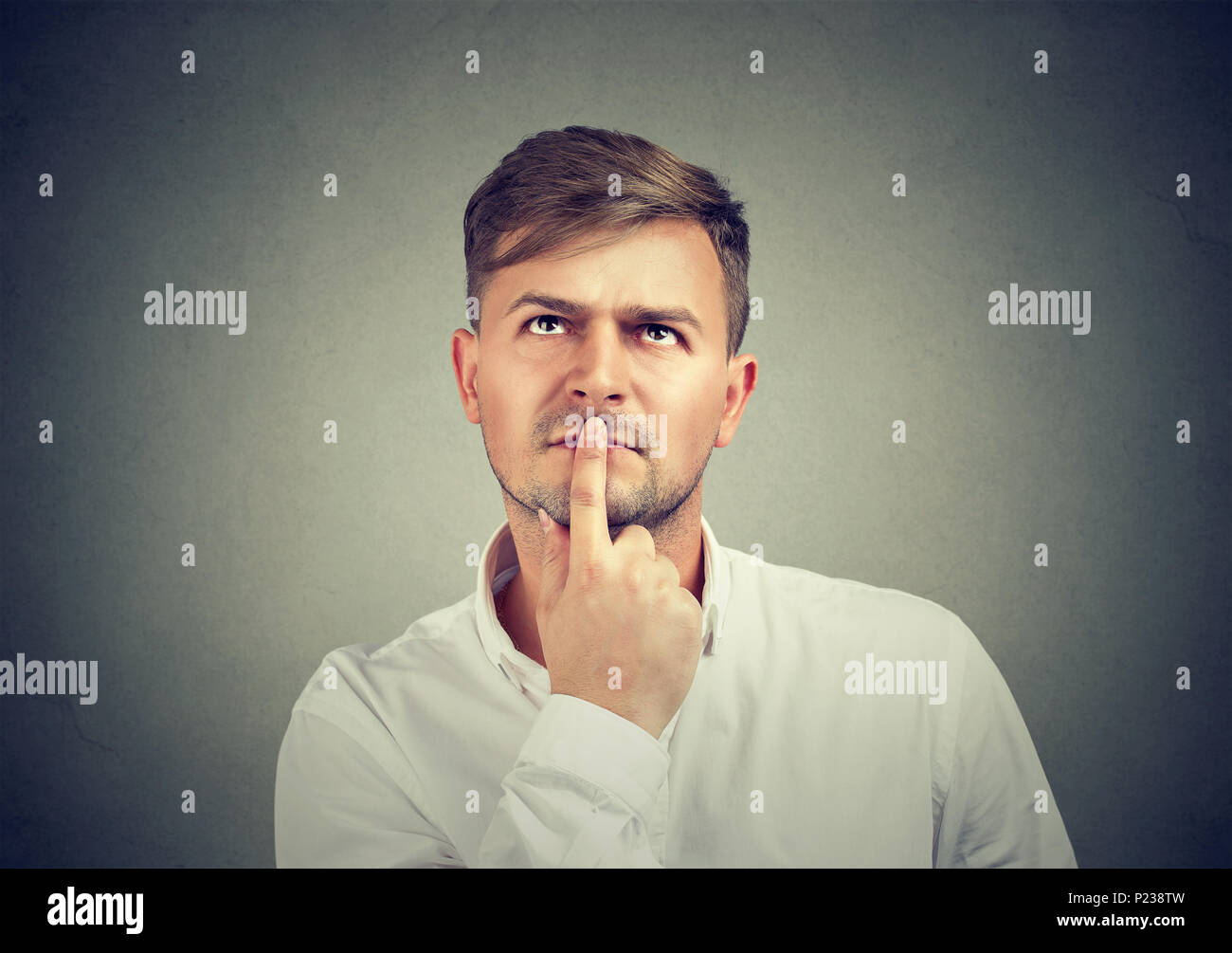 Handsome casual man in white shirt touching lips with finger and thinking on problem looking up. - Stock Image