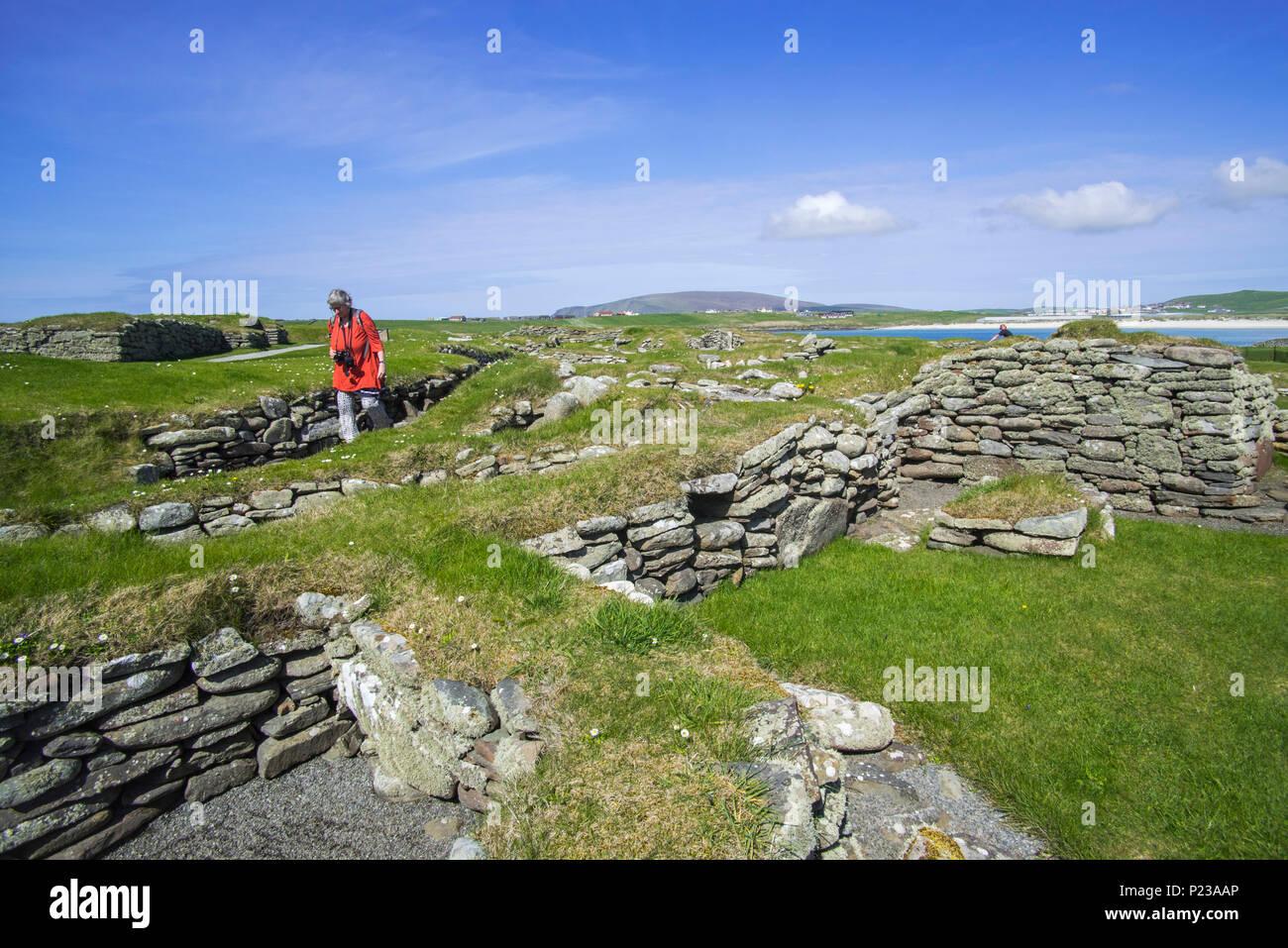 Tourist visiting Jarlshof, archaeological site showing 2500 BC prehistoric and Norse settlements at Sumburgh Head, Shetland Islands, Scotland, UK - Stock Image
