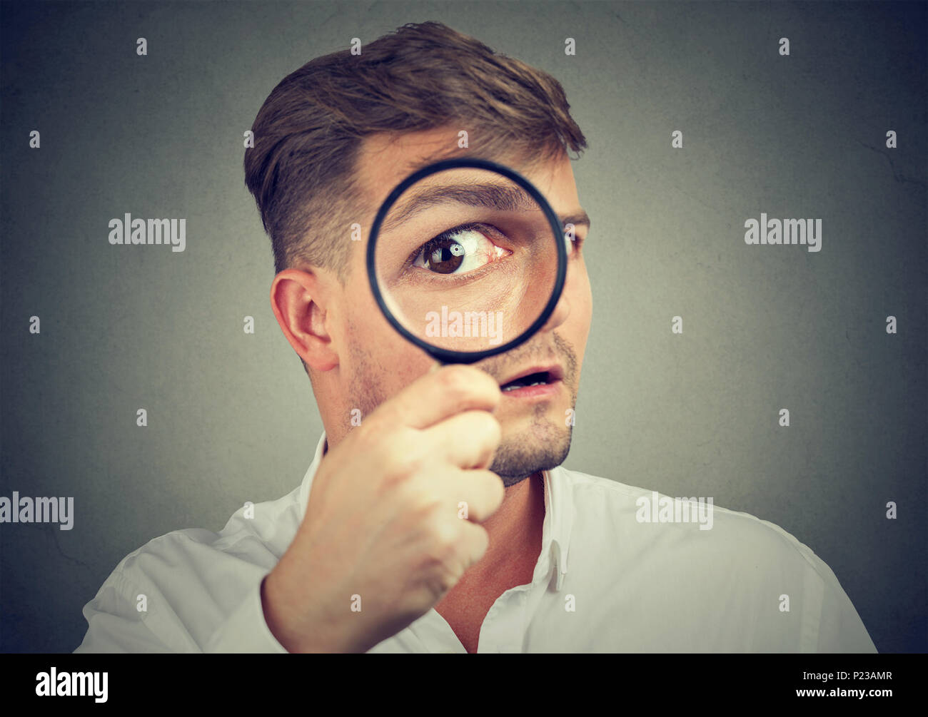Young expressive man looking shocked while looking at camera through magnifier. - Stock Image