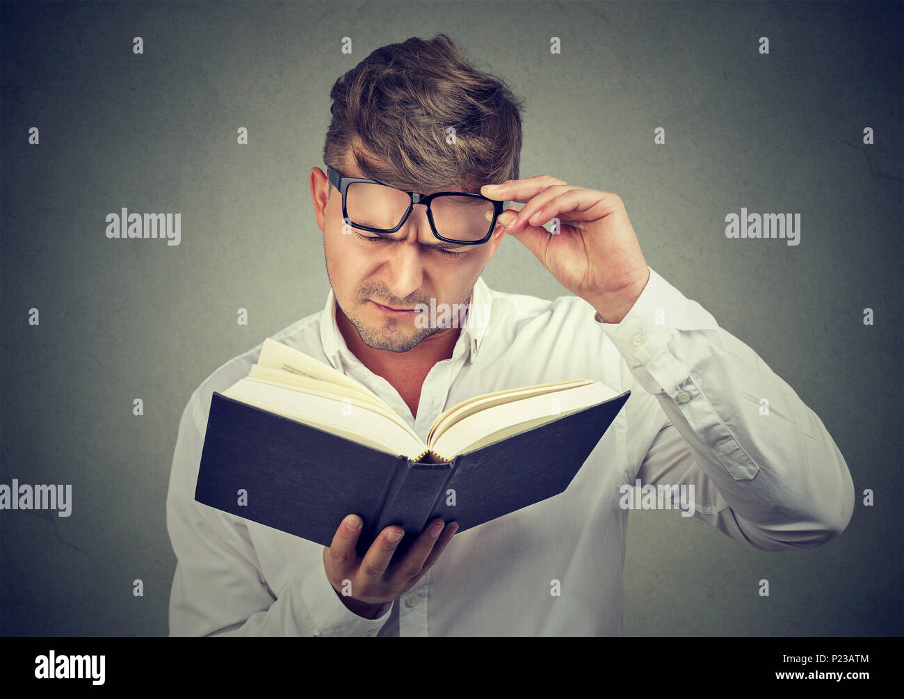 Young man frowning eyebrows while lifting eyeglasses and trying to read book on gray background. - Stock Image