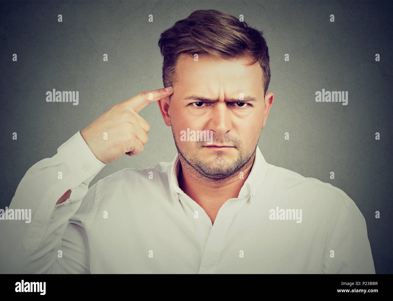 Serious upset man pointing at temple with forefinger and looking at camera anxiously. - Stock Image