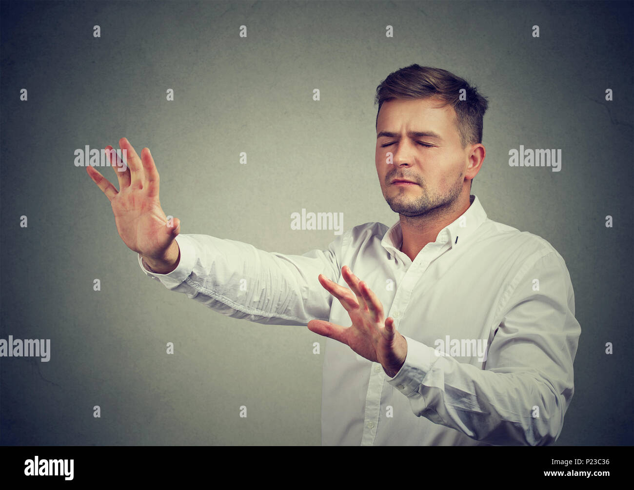 Young man with eyes closed pushing hands forward walking in darkness with help of intuition. - Stock Image