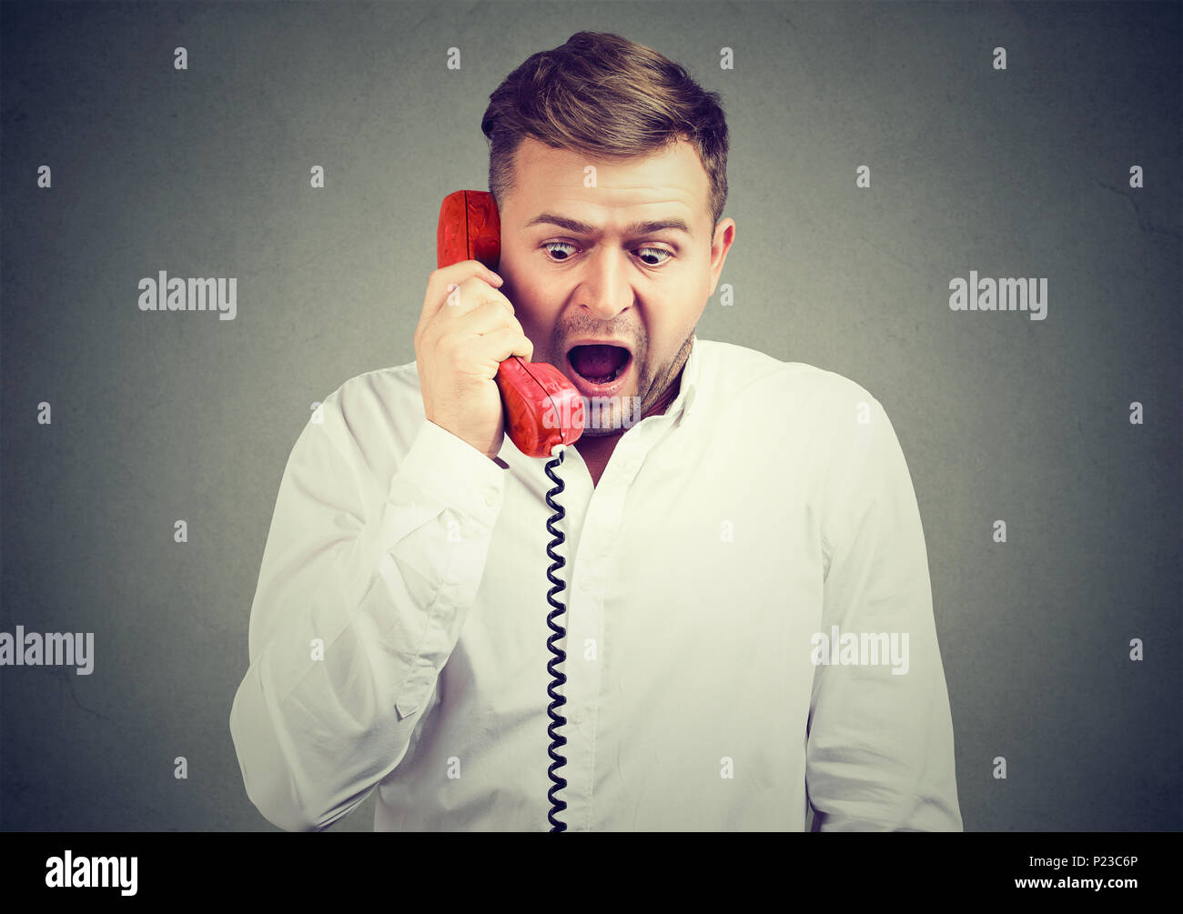 Expressive screaming man speaking on a phone being stunned with bad news and reacting. - Stock Image